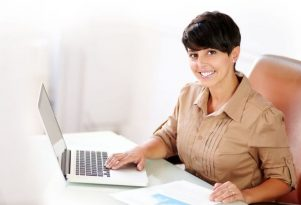woman on a mac laptop processing online no credit check cash loan applications