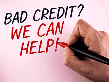 hand with pen and writing bad credit we can help